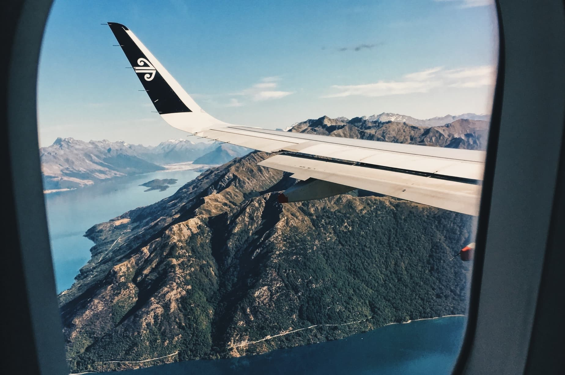 View from an airplane window at the wings and flying over a scenic landscape of green hills and rivers as you arrive in New Zealand