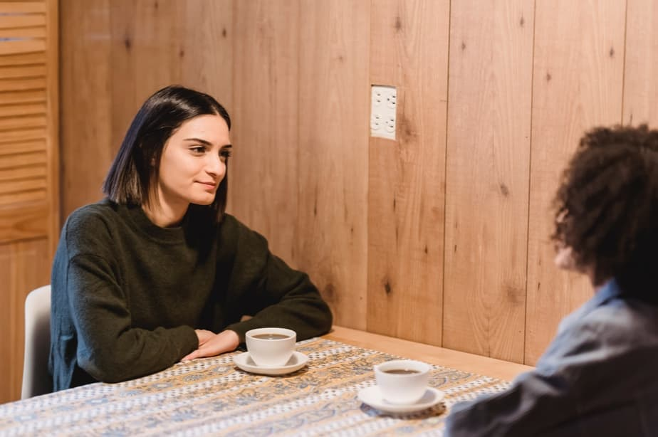 Woman interviewing another woman and they having coffee together in a room
