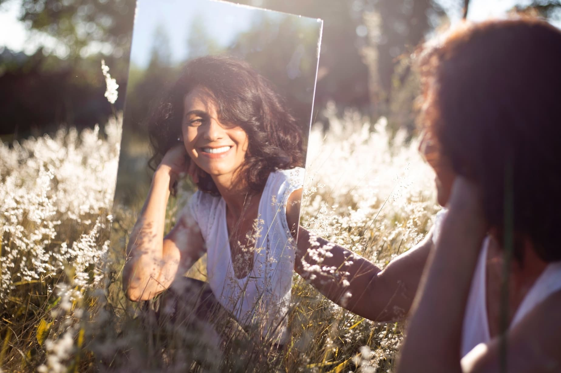 woman holding mirror outdoors in nature looking at herself